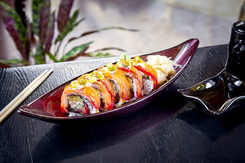 Sushi moderno do rolo do japonês da culinária com queijo creme e salmões Vista ascendente próxima no sushi com abacate e salmões  imagem de stock royalty free