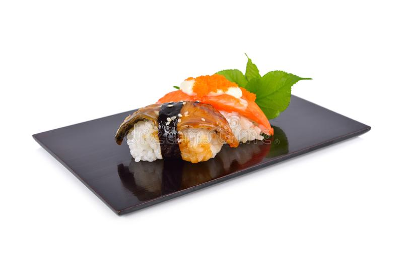 Sushi nigiri and sashimi served on flat black plate with white background stock images