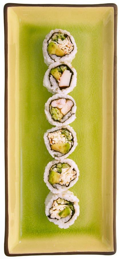 Sushi op een groene plaat die op wit wordt geïsoleerdl royalty-vrije stock foto
