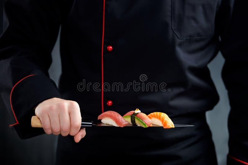 Sushi op Japans mes in chef-kokhand die worden gediend stock foto's
