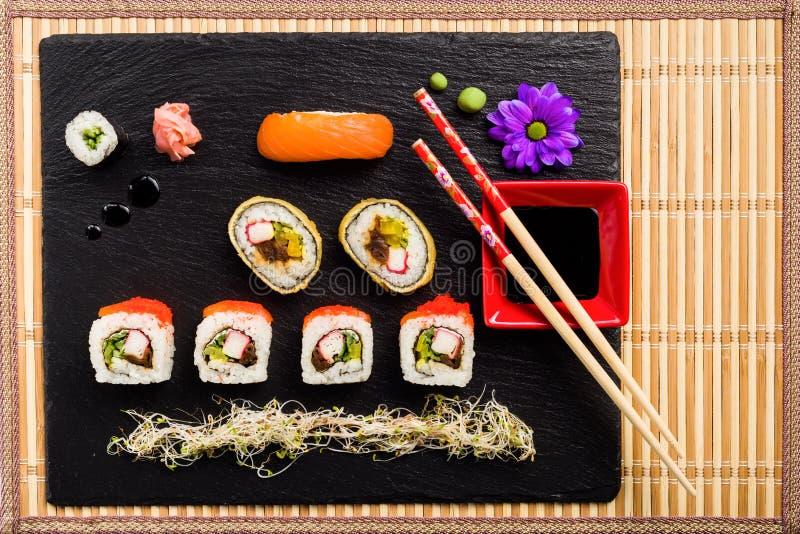 Sushi på den svarta stenplattan på en matt bambu arkivbild