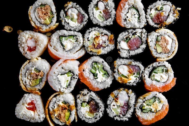 Sushi på en svart bakgrund Sushiuppsättning på en tabell Top beskådar Asiatisk eller japansk mat arkivfoto