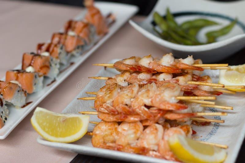 Sushi på en tabell Räkor, tigerrullar och edamame på vit plat arkivfoton