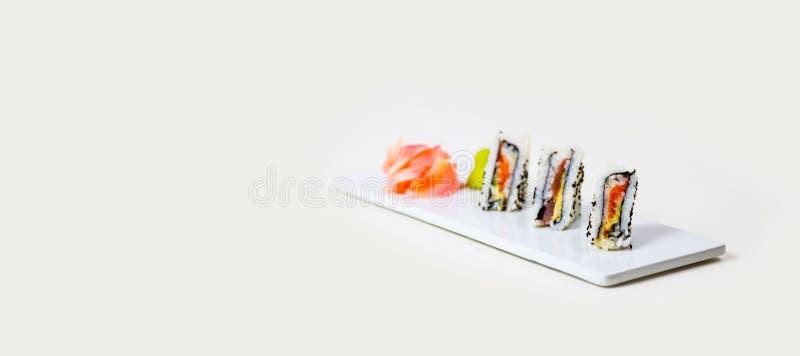 Sushi på en vit platta på en vit bakgrund royaltyfria foton