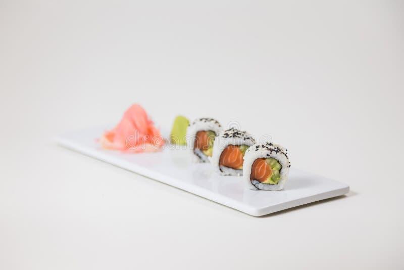 Sushi på en vit platta på en isolerad vit bakgrund arkivbilder
