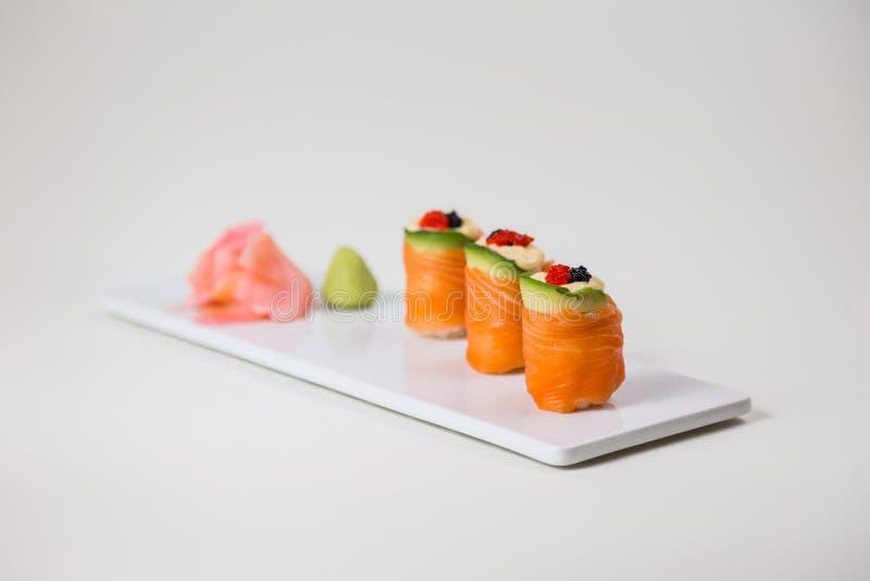 Sushi på en vit platta på en isolerad vit bakgrund royaltyfria bilder
