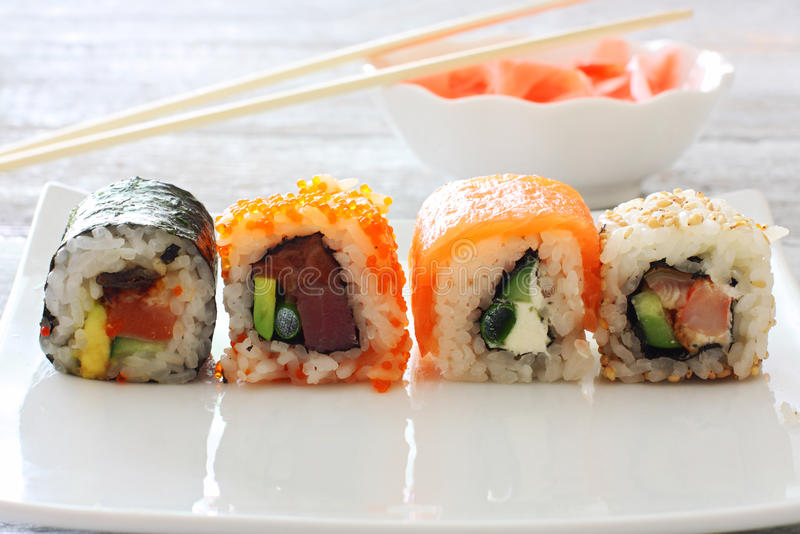 Sushi pieces collection. On white plate over wood table stock photography