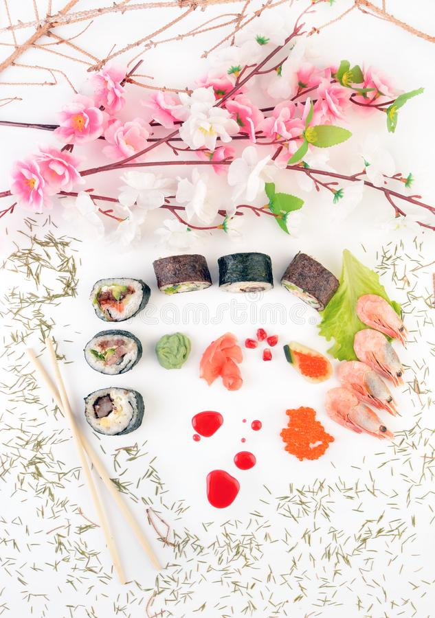 Sushi pieces are decorated with artificial flowers and fir needles. Japanese traditional cuisine. view from above royalty free stock photography