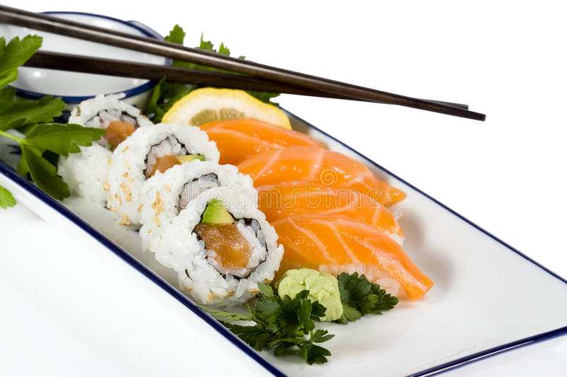Sushi on plate. Salmon sushi and sushi rolls on white and blue plate with chopsticks