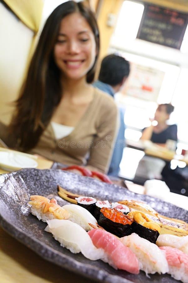 Sushi que come o turista da mulher no restaurante do Tóquio imagem de stock