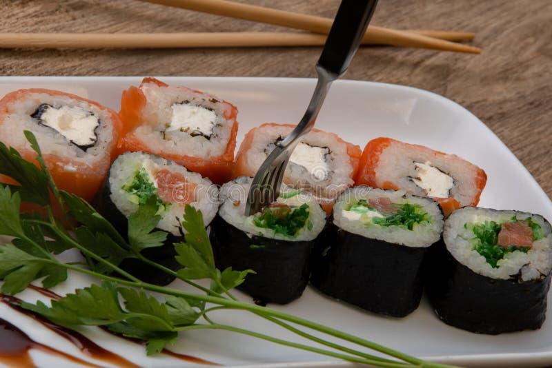Sushi reihten mit einer Gabel, japanische Rollen, Fische und Reis auf, stockbild