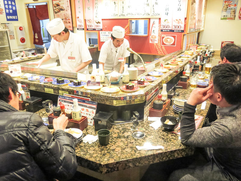 Sushi restaurant in Tokyo. TOKYO,JAPAN - FEBRUARY 11,2015: people eating in a Sushi restaurant in Tokyo.Sushi is a traditional japanese speciality known all over royalty free stock photography