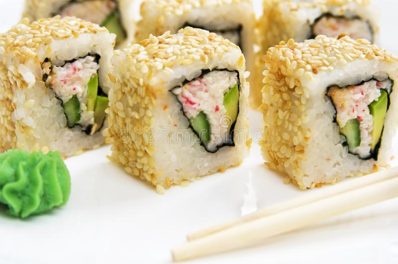 Sushi roll with avocado, vegetables and sesame on a white plate. stock images