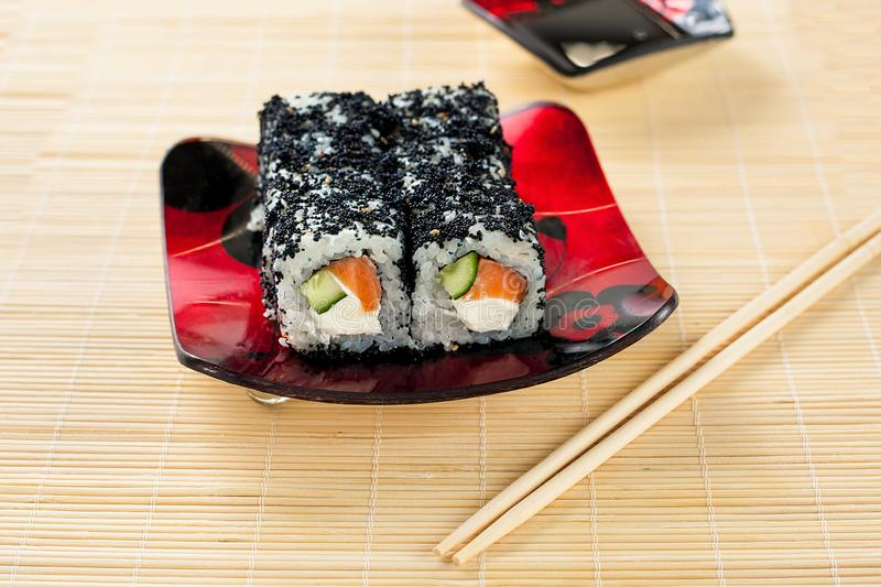 Sushi roll with black caviar on a plate stock image