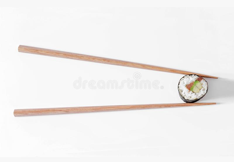 Sushi roll in black chopsticks isolated on white background. Japanese cuisine. Sushi roll in wooden chopsticks isolated on white background. Japanese cuisine stock photo
