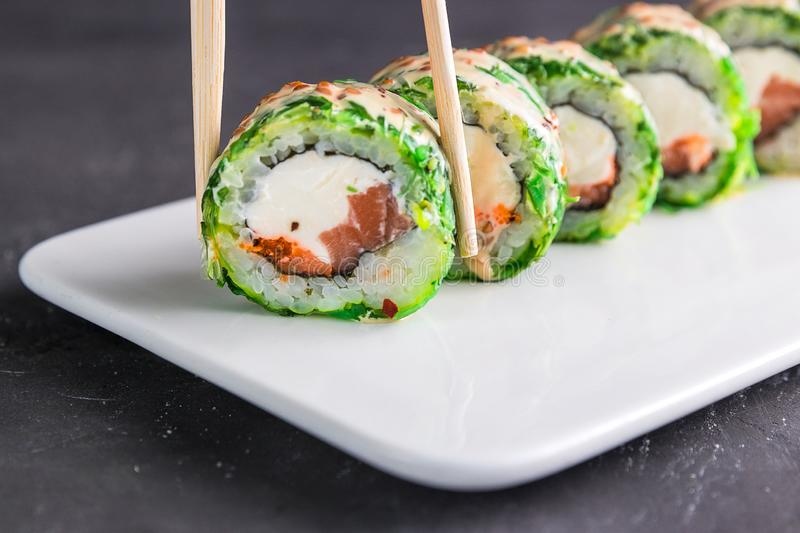 Sushi roll with chopsticks on a white plate close up. Closeup view of japanese food in restaurant stock image