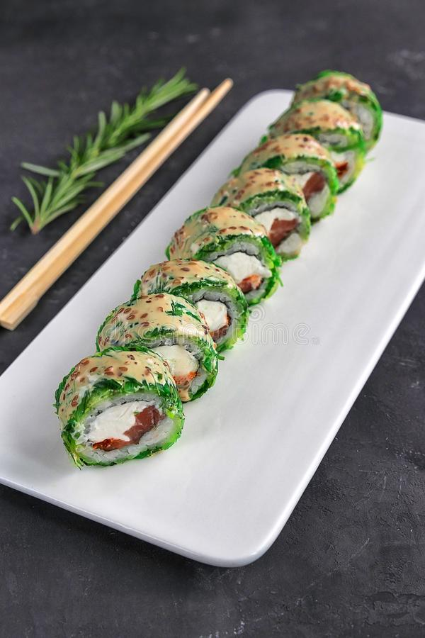 Sushi roll with chopsticks on a white plate and rosemary. Closeup view of japanese food in restaurant royalty free stock image