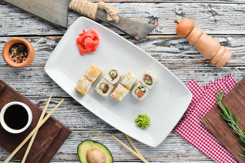Sushi roll with fish, avocado and cucumber. Chinese traditional dish. Top view. Free copy space royalty free stock photo
