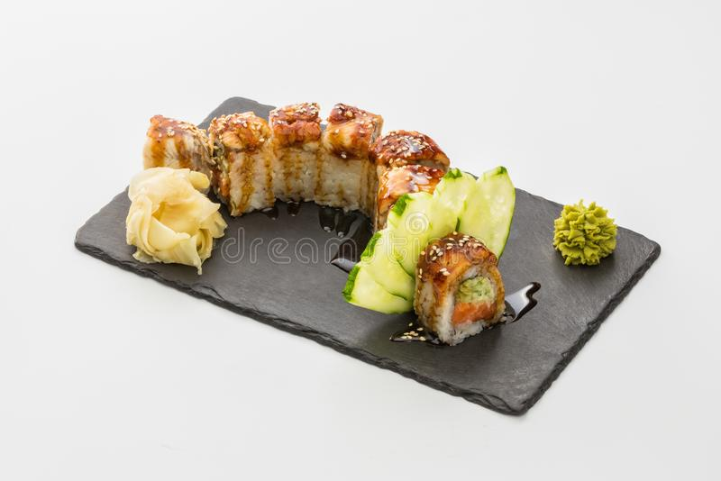 Sushi roll of red dragon in black stone plate isolated on white stock photos