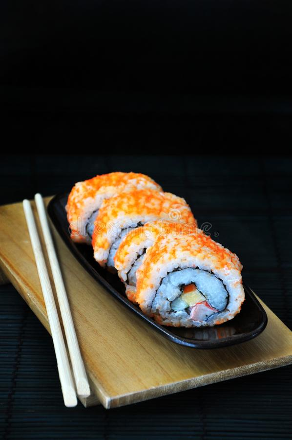 Sushi Roll top with Fish eggs. Japanese dish sushi roll top with fish eggs put on wooden board royalty free stock photos