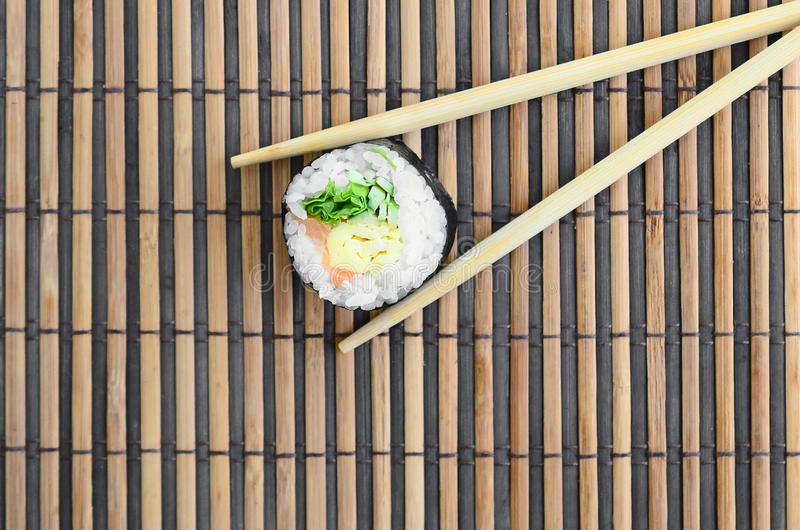 Sushi roll and wooden chopsticks lie on a bamboo straw serwing mat. Traditional Asian food. Top view. Flat lay minimalism shot. With copy space royalty free stock photos