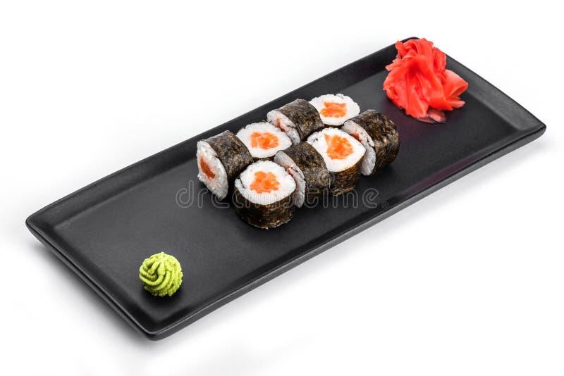 Sushi-Rolle - Maki Sushi mit Lachs- und Frischkäse auf dem Schwarzblech lokalisiert über weißem Hintergrund stockfotografie