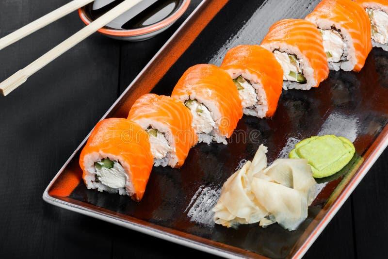 Sushi-Rolle - Maki Sushi gemacht vom Avocado und Frischkäse der Lachse, der Gurke, auf dunklem hölzernem Hintergrund stockfotos