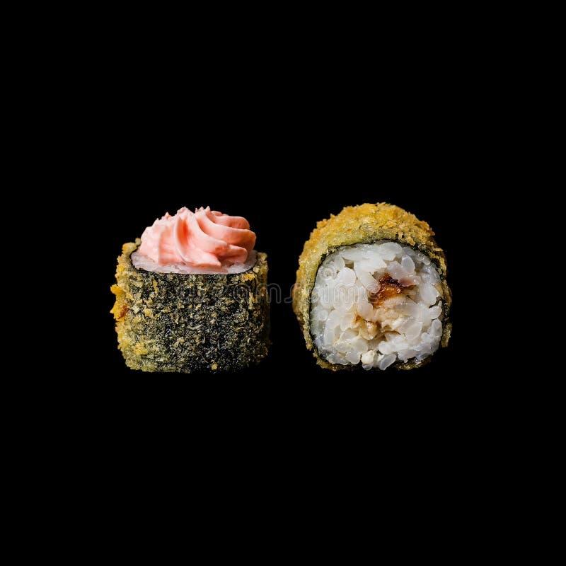 Sushi Rolle mit Aal Tempura und Frischkäse, lokalisiert im schwarzen Hintergrund stockfoto