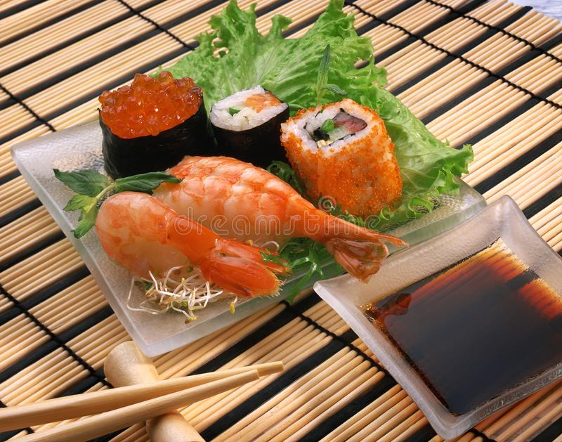 Sushi, Rollen, Garnelen, roter Kaviar, Sojasoße stockbild