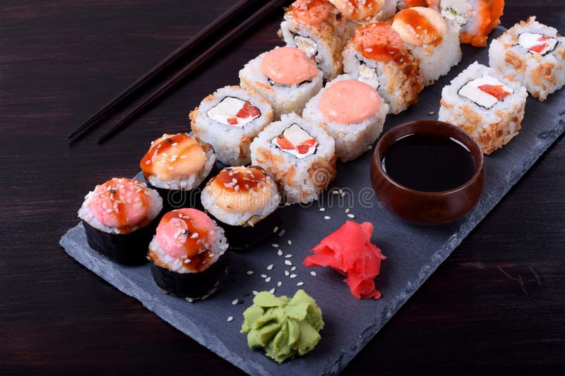 Sushi rolls assortment, wasabi, marinated ginger, soy sauce served on slate plate royalty free stock photos