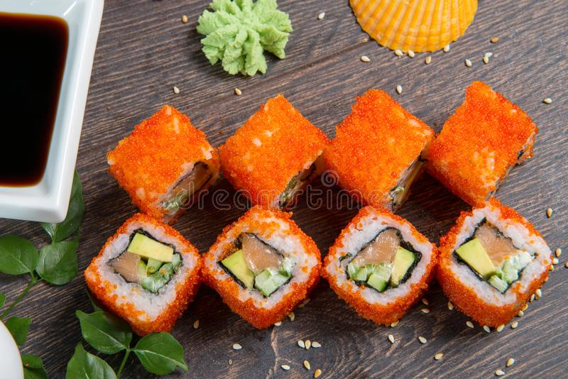 Sushi rolls and caviar on black wooden table. Japanese food. royalty free stock photo