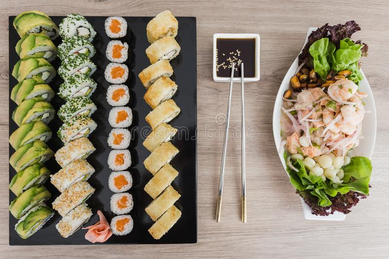 Sushi rolls with ceviche and soy sauce on a wooden table royalty free stock images