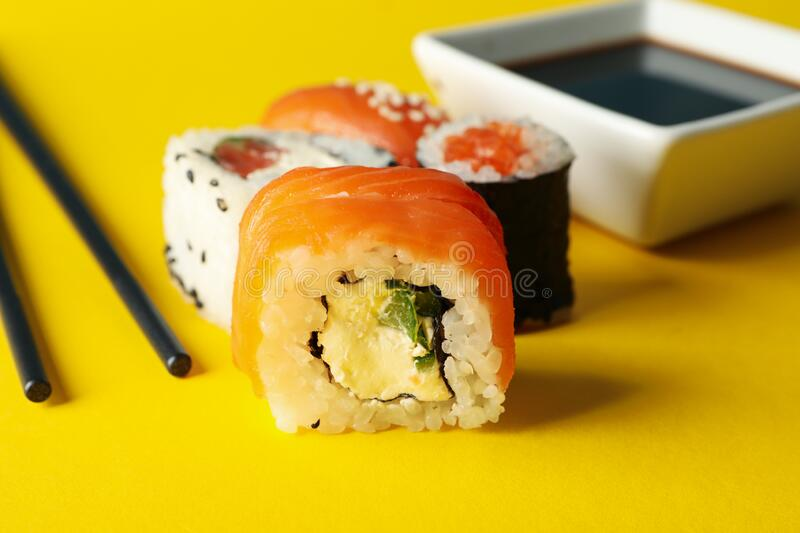 Sushi rolls, chopsticks and soy on background, close up. Sushi rolls, chopsticks and soy on yellow background, close up stock photos