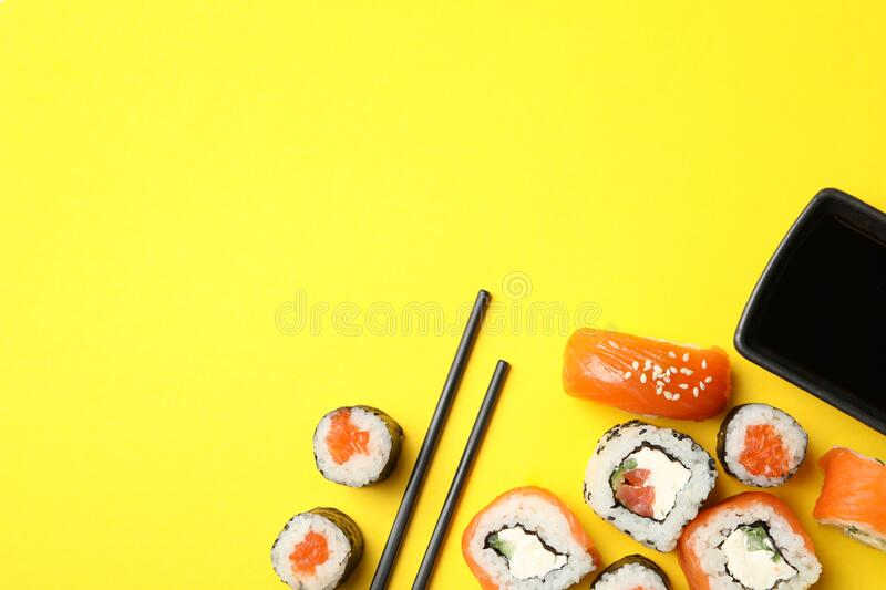Sushi rolls, chopsticks and soy on background, top view. Sushi rolls, chopsticks and soy on yellow background, top view stock image