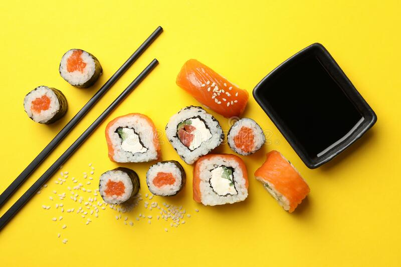 Sushi rolls, chopsticks and soy on background, top view. Sushi rolls, chopsticks and soy on yellow background, top view stock photography