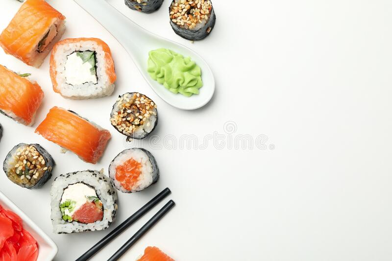Sushi rolls and chopsticks on background, space for text. Japanese food. Sushi rolls and chopsticks on white background, space for text. Japanese food stock images