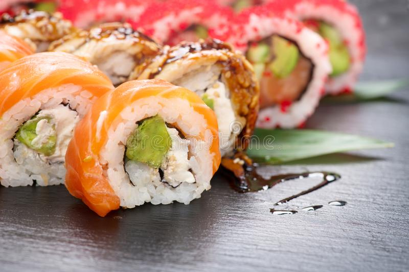 Sushi rolls closeup. Japanese food in restaurant. California sushi roll set with salmon, eel, vegetables and flying fish caviar. On black slate background stock photo