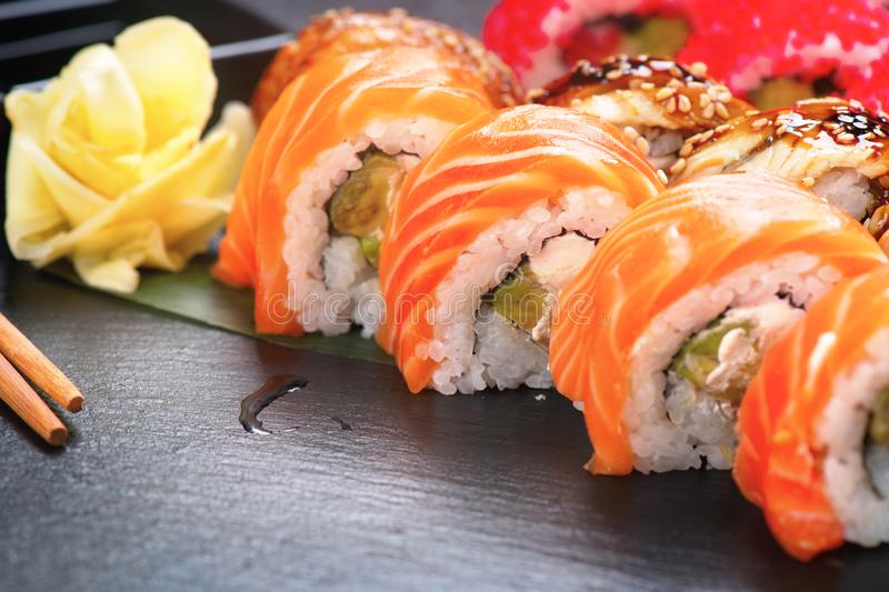 Sushi rolls closeup. Japanese food in restaurant. Roll with salmon, eel, vegetables and flying fish caviar. On black slate background stock image