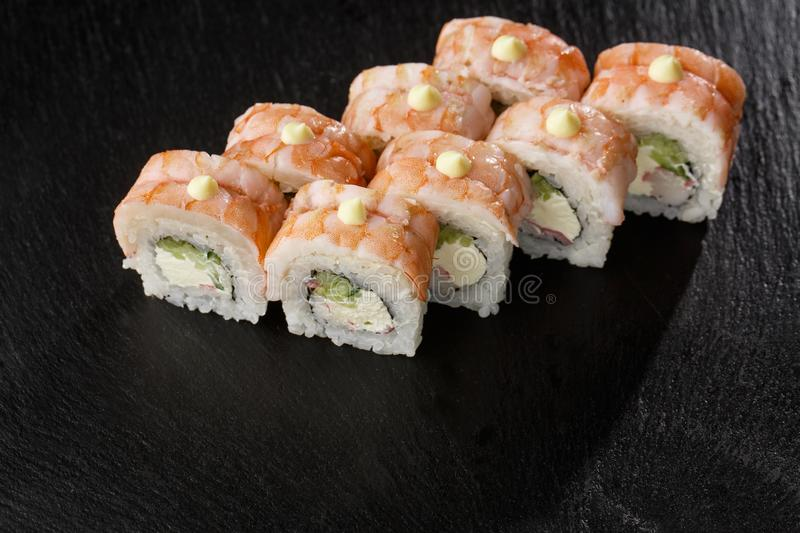 Sushi Rolls with cucumber, shrimp, crab meat and Cream Cheese inside on black slate isolated. Philadelphia roll sushi royalty free stock photography