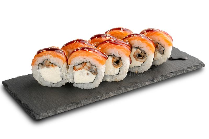 Sushi Rolls with eel and salmon and Cream Cheese inside on black slate or stone shale surface isolated. On white background stock image