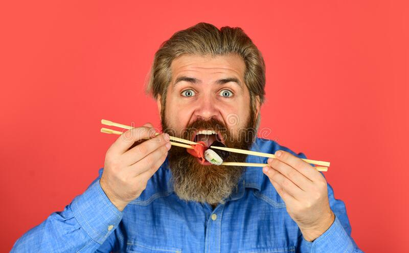Sushi rolls. Japanese cuisine. Asian meal. Sushi roll. Man eat sushi chopsticks. Eastern culture. Bearded hipster eating. Rolls. Japanese food delivery. Pickled royalty free stock image