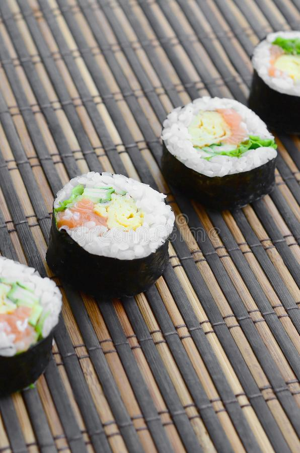 Sushi rolls lies on a bamboo straw serwing mat. Traditional Asian food royalty free stock images