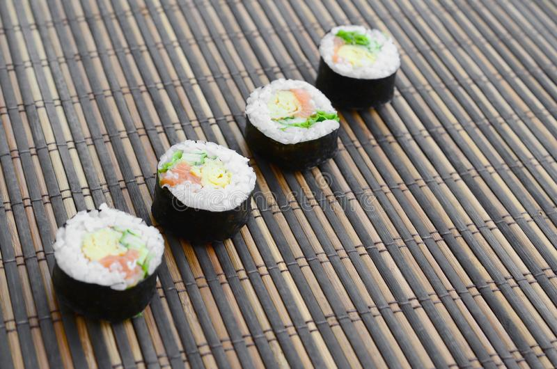 Sushi rolls lies on a bamboo straw serwing mat. Traditional Asian food stock photo