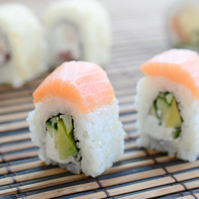Sushi rolls lies on a bamboo straw serwing mat. Traditional Asian food. Shallow depth of field stock photography