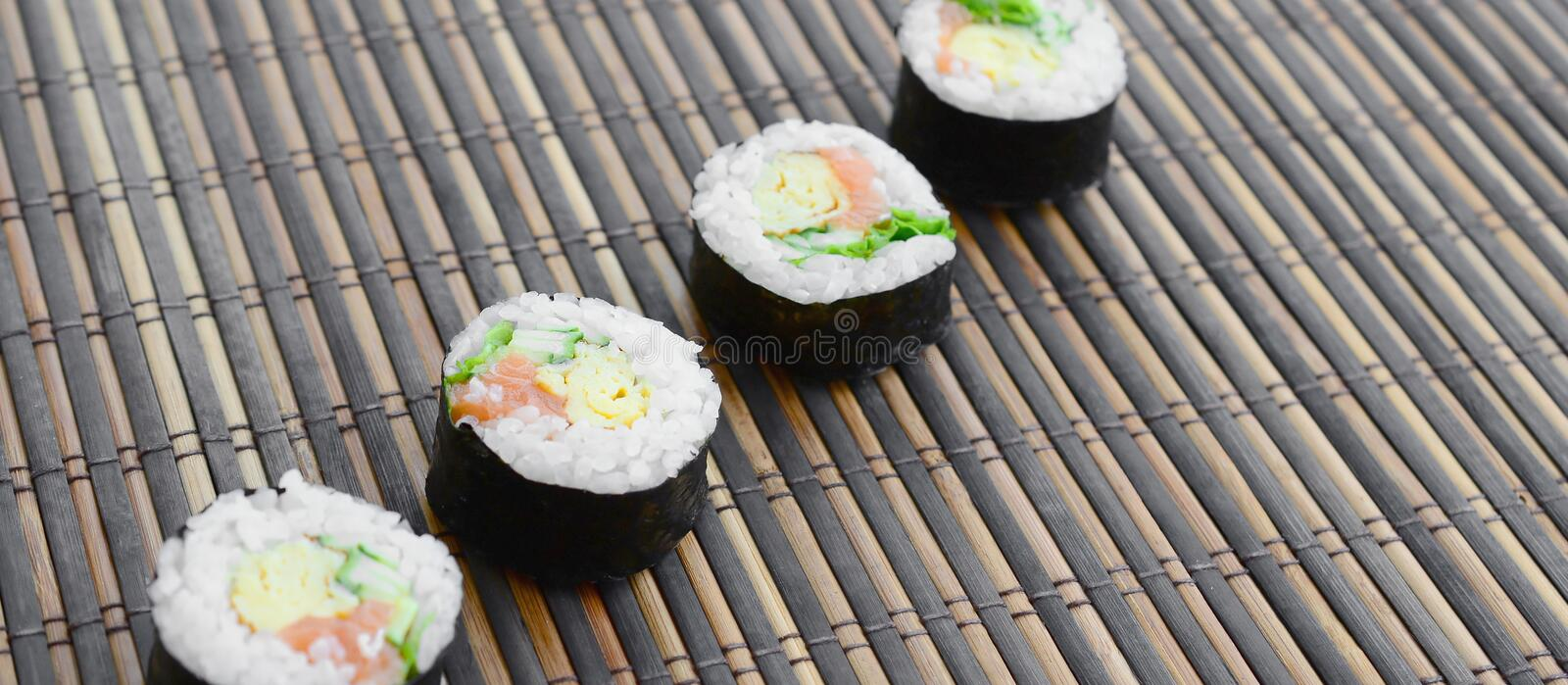 Sushi rolls lies on a bamboo straw serwing mat. Traditional Asian food stock images