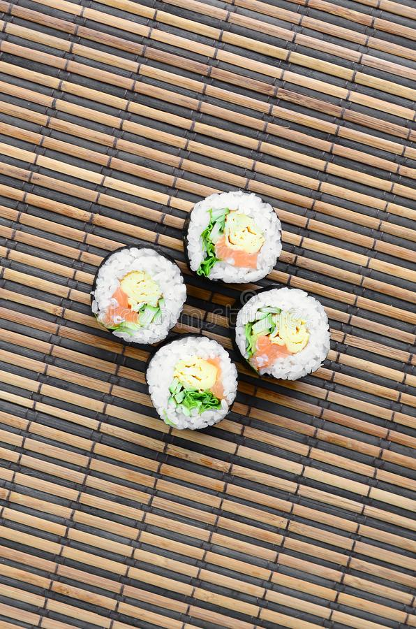 Sushi rolls lies on a bamboo straw serwing mat. Traditional Asian food. Top view. Flat lay minimalism shot with copy space royalty free stock photography