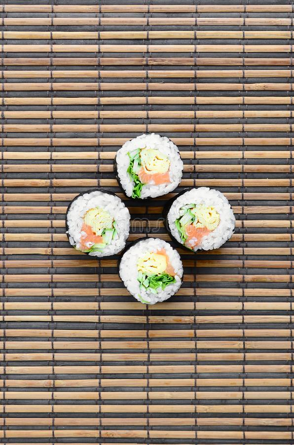 Sushi rolls lies on a bamboo straw serwing mat. Traditional Asian food. Top view. Flat lay minimalism shot with copy space stock photos