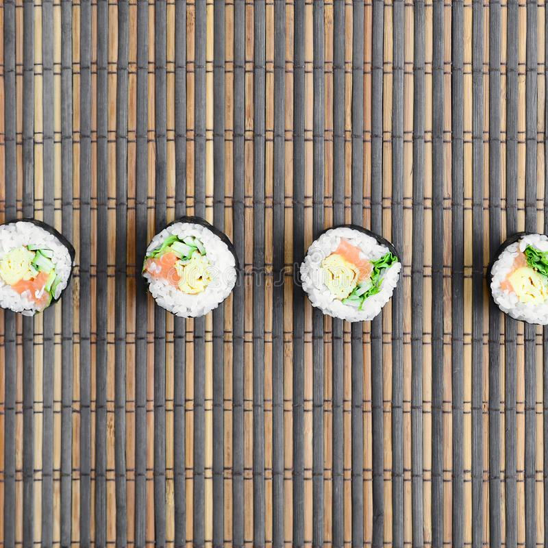 Sushi rolls lies on a bamboo straw serwing mat. Traditional Asian food. Top view. Flat lay minimalism shot with copy space royalty free stock image
