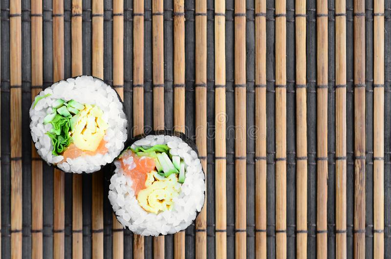 Sushi rolls lies on a bamboo straw serwing mat. Traditional Asian food. Top view. Flat lay minimalism shot with copy space stock images