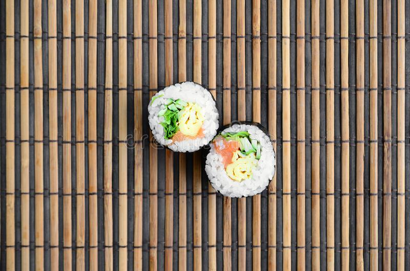 Sushi rolls lies on a bamboo straw serwing mat. Traditional Asian food. Top view. Flat lay minimalism shot with copy space royalty free stock photo